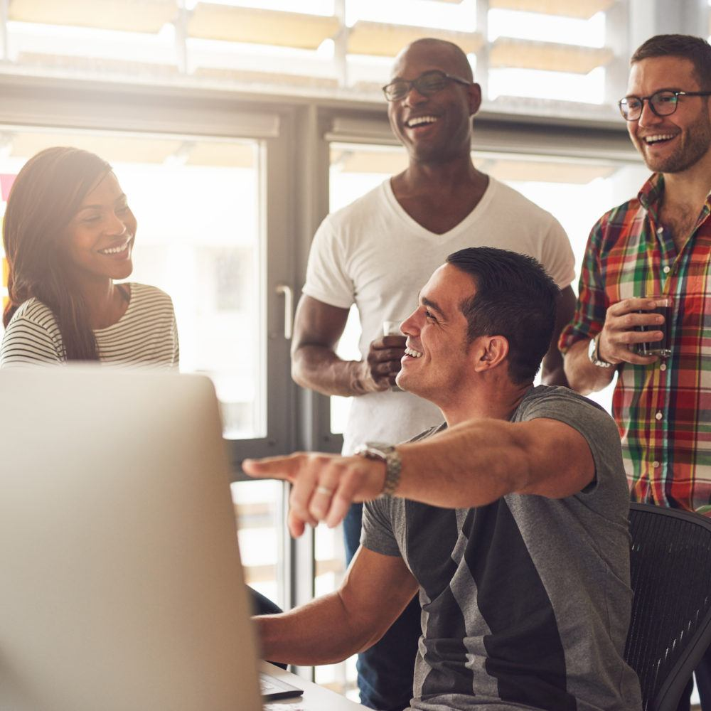 group of people smiling and pointing at a computer
